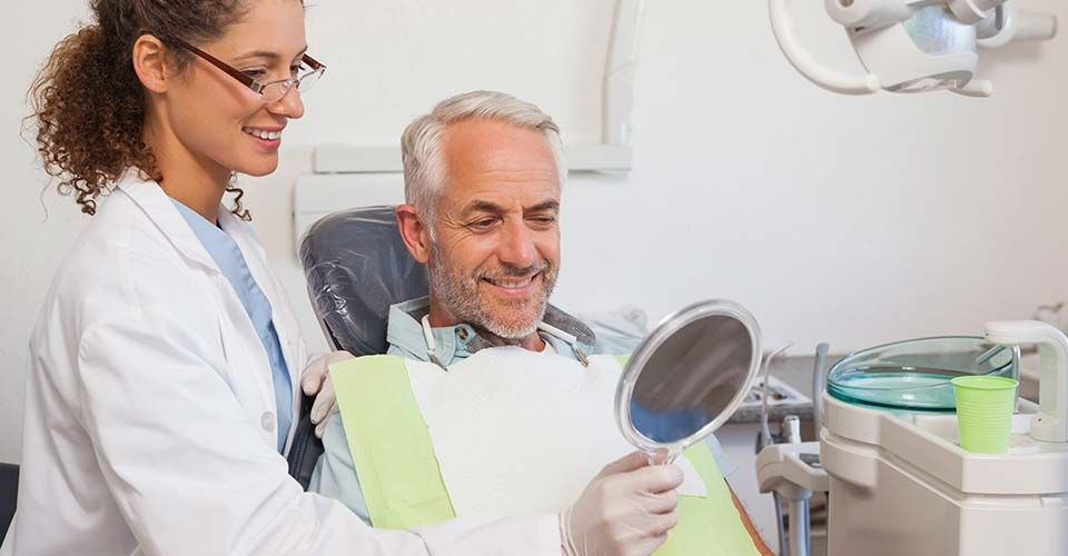 Dentist showing patient his new smile in the mirror at the dental clinic